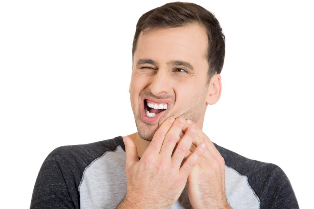 a man holds his jaw in pain | st paul dentist