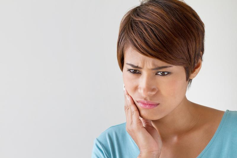 A Woman Holds Her Jaw In Pain | Emergency Dentistry St. Paul, MN
