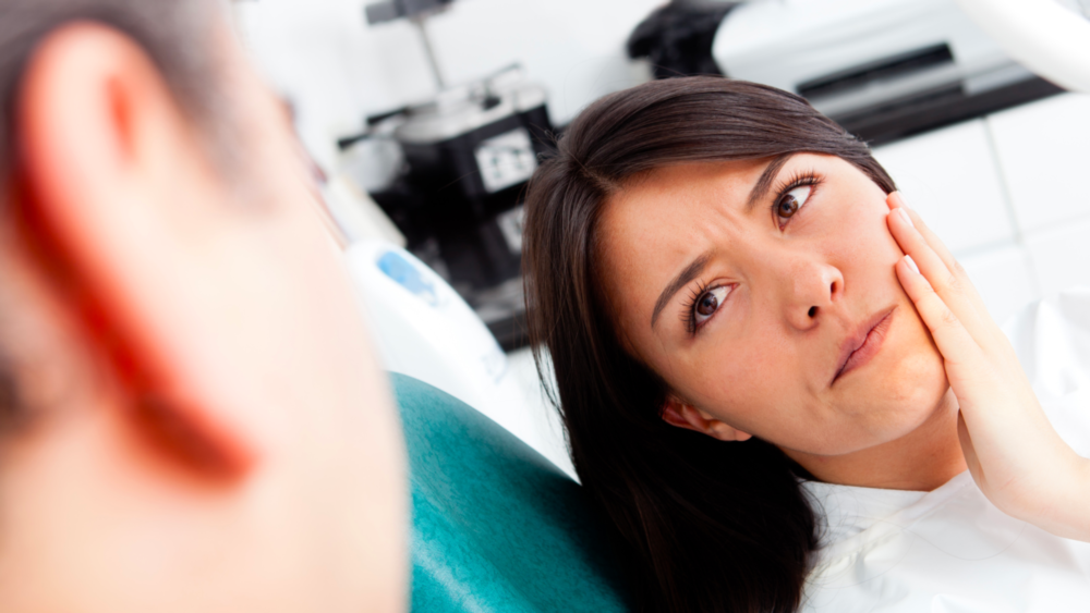 A woman sits in the dental chair, looking at the dentist with concern | Emergency Dentist in St. Paul MN