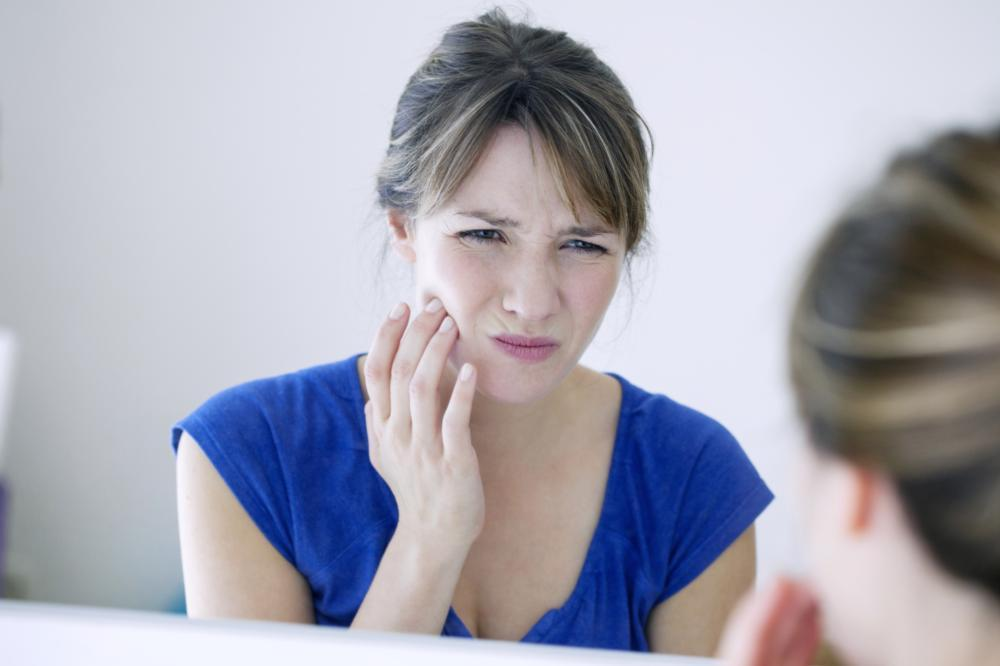 A woman looks in the mirror, holding her hand up to her jaw in pain | dentist 55116