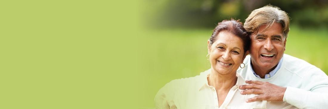 elderly dark haired man and woman smiling against a green outdoor spring background