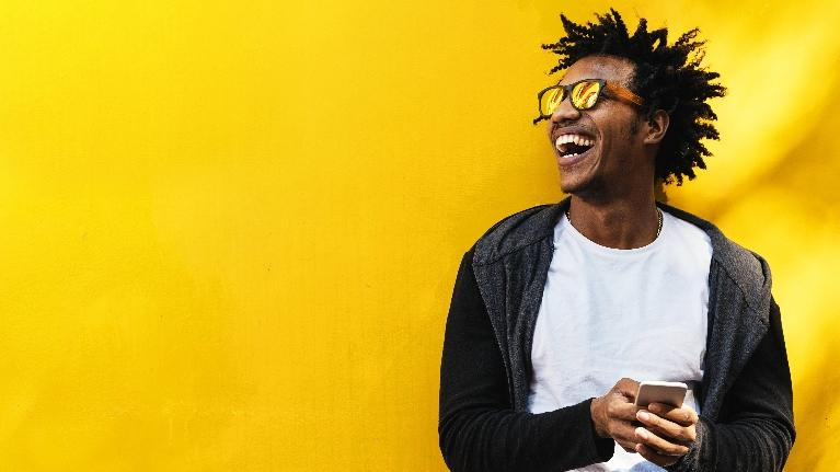 A man smiles in front of a yellow wall | Cosmetic dentist st paul