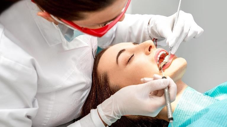 a picture of a woman getting her gums worked on by a dentist | top dentist st paul mn