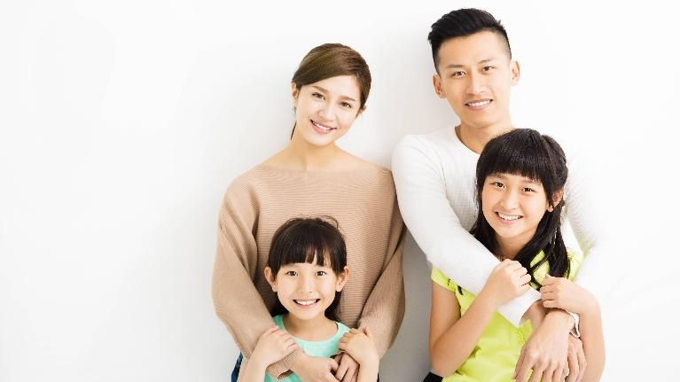 A family smiles in front of a wall | St. paul family dentist