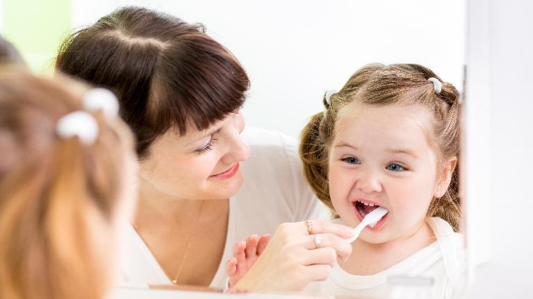 a woman brushes her daughter's teeth | pediatric dentist in st. paul