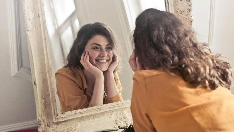 A woman smiles at her self in the mirror | Cosmetic Dentist St. Paul MN